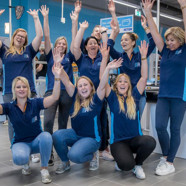 Groep van enthousiaste Action medewerkers in een Action winkel