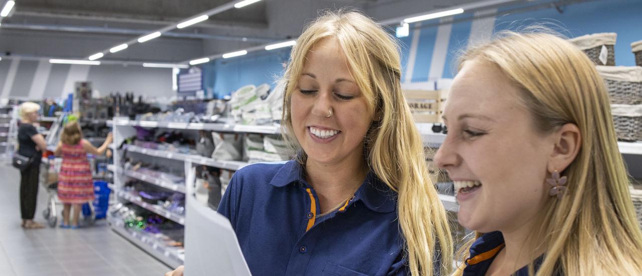Afbeelding van twee Action medewerkers die een document lezen