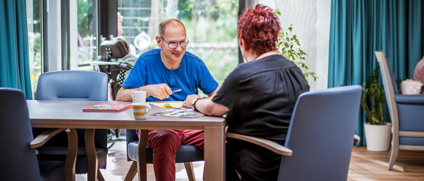 Vrouw zit met man lachend om tafel