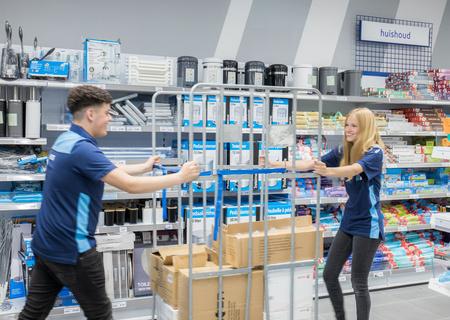 Afbeelding van twee Action collega's die een magazijnwagen duwen