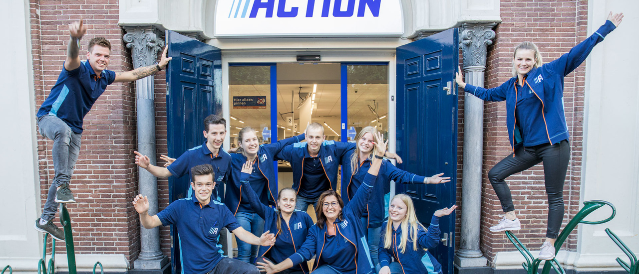 Enthusiastic group of Action employees in front of an Action store