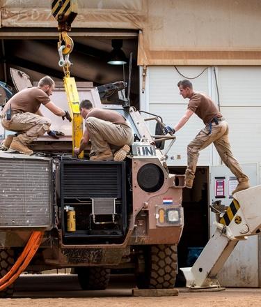 Militairen van het herstel poloton repareren een Bushmaster voertuig
