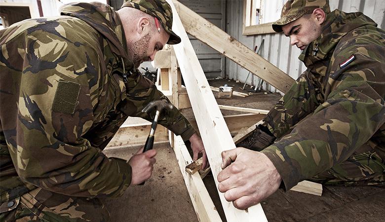 Soldaten timmeren aan een houten frame