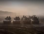 Tanks rijden in formatie over een veld