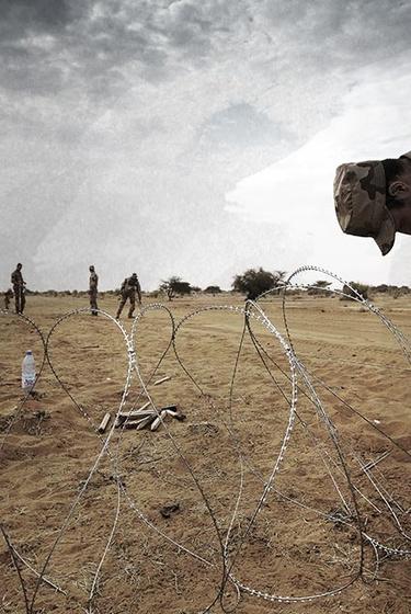 Soldaat maakt een hek van prikkeldraad