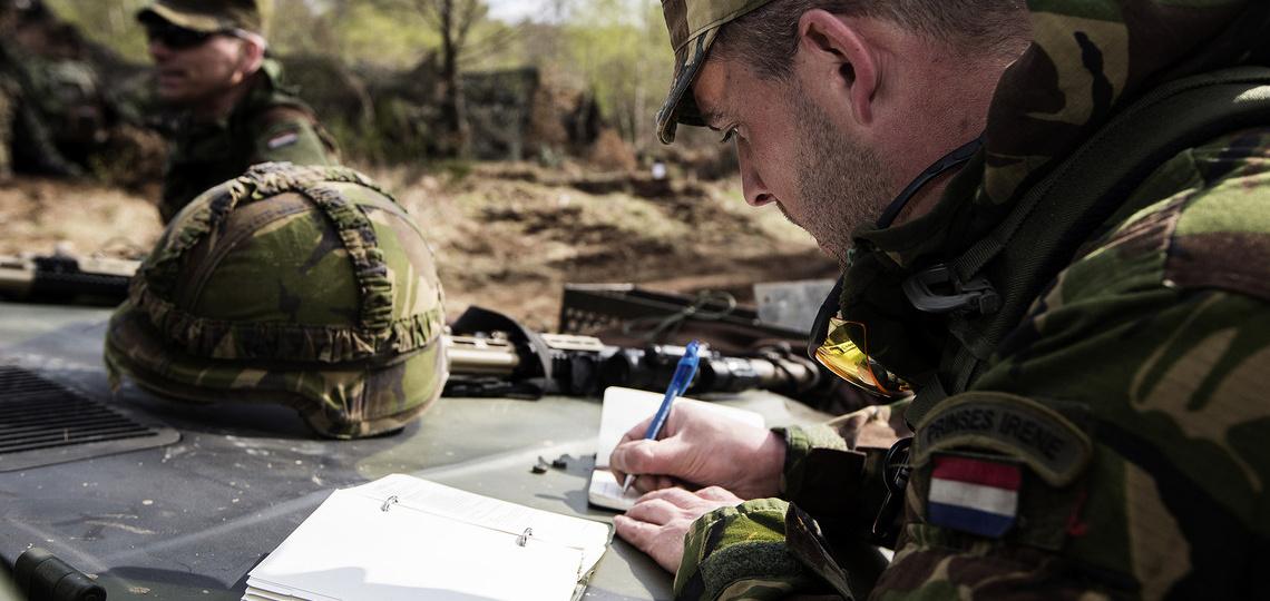 Militair schrijft in een boekje