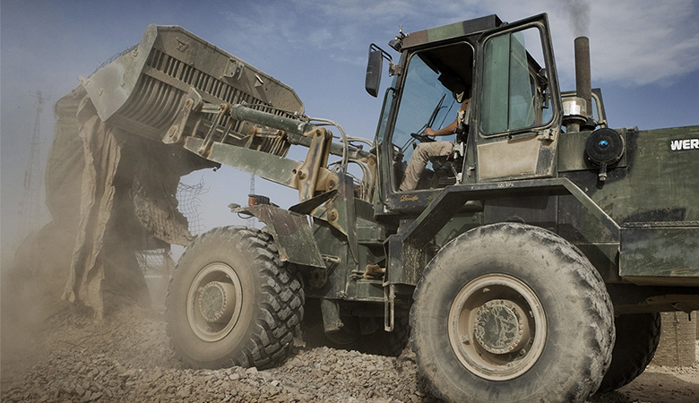 Man in tractor ruimt grote stukken afval op