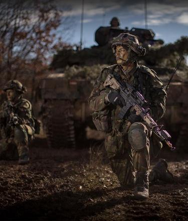 Infanteristen wachten voor een tank