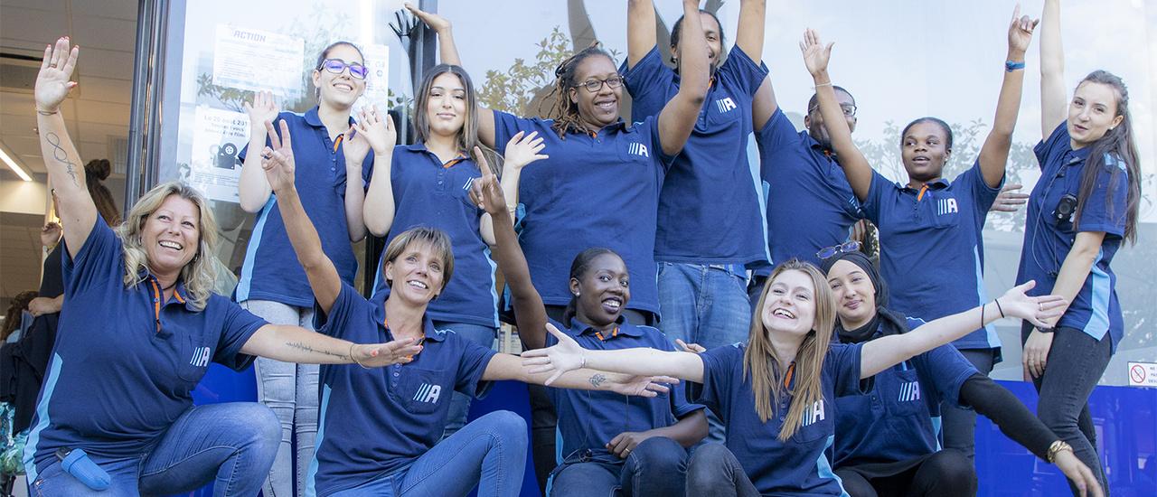Un groupe d'employés d'Action enthousiastes devant un magasin Action
